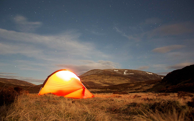 Eine Nachtaufnahme eines von innen erleuchteten Iglu-Zeltes vor einer kargen, nordeuropäischen Landschaft und einem Sternenhimmel.